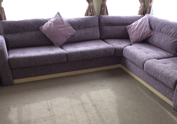 A newly furnished static caravan interior with matching seat cushions, scatter cushions and curtains
